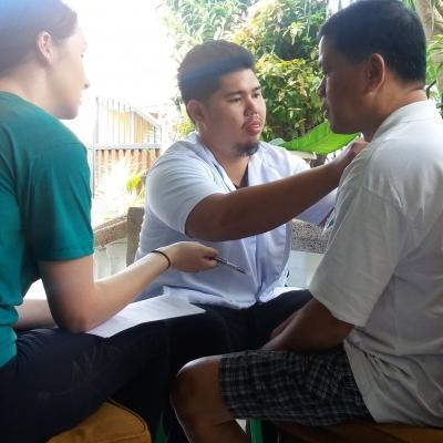 A student on the Physiotherapy internship for teenagers in the Philippines, observes as staff assist a man.